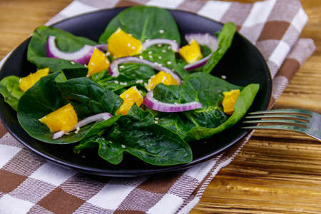 Tasty salad with spinach, orange, red onion and sesame seeds on wooden table. Healthy food or vegetarian concept Archivio Fotografico