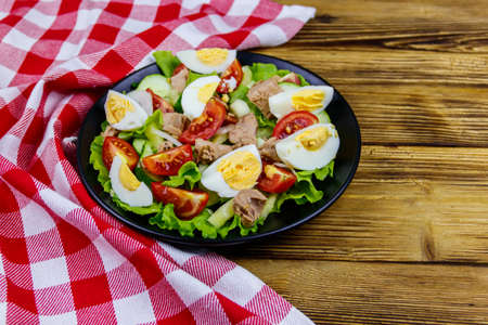 Tasty tuna salad with eggs, lettuce and fresh vegetables on wooden table Archivio Fotografico