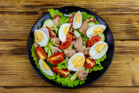 Tasty tuna salad with eggs, lettuce and fresh vegetables on wooden table. Top view