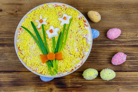 Traditional russian layered salad Mimosa with spring decoration Daffodil and easter eggs on wooden table. Top view. Decoration is made of egg, green onion and carrot