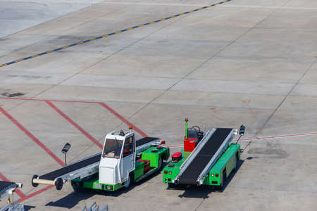 Belt luggage loader vehicles in the airport Archivio Fotografico