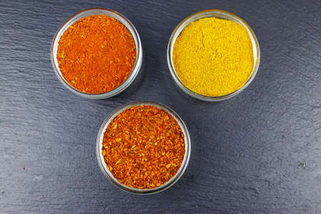Set of different aromatic spices on black slate. Top view