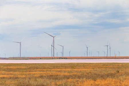 Wind turbines on a shore of the pink salty Syvash lake in Kherson region, Ukraine. Renewable energy