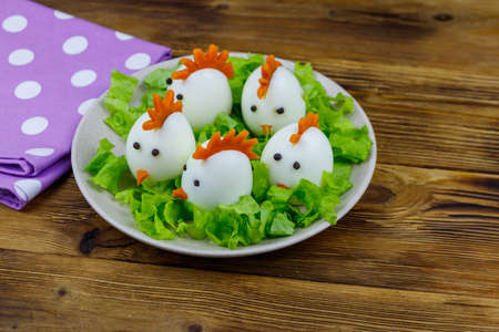 Funny easter breakfast with boiled eggs as chicks on wooden table