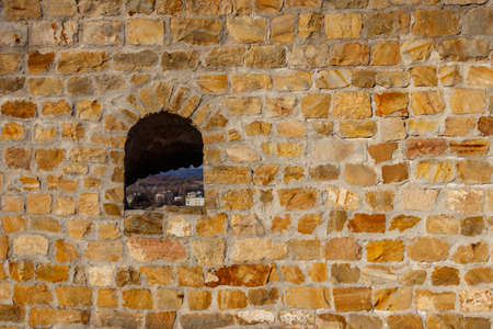 Background of the old stone wall with a loophole