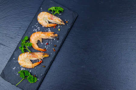 Big raw red prawns with parsley, salt and pepper on a slate board on black background. Top view, copy space