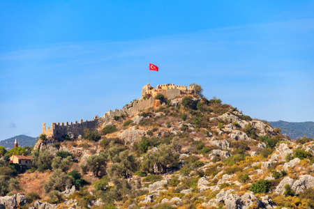 View of ancient Lycian town Simena with fortress on a mount on the coast of the Mediterranean sea in Antalya Province, Turkey