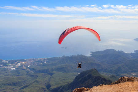 Paragliders flying from a top of Tahtali mountain near Kemer, Antalya Province in Turkey. Concept of active lifestyle and extreme sport adventure