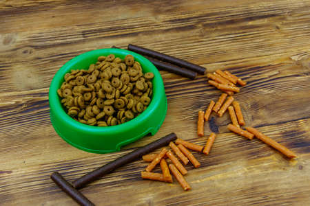 Dog delicacy food and feed in green plastic bowl on wooden background. Dog care concept 免版税图像