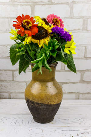 Bouquet of flowers in antique rustic clay jug against white brick wall