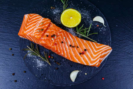 Raw salmon fillet with spices on black slate. Top view 免版税图像