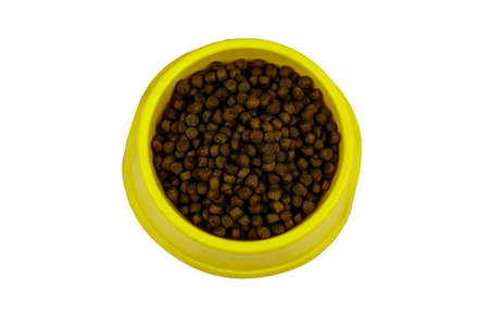 Dry food for cat or dog in a bowl. Top view. Pet food isolated on white background 免版税图像