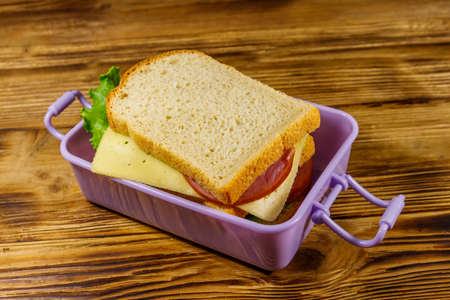 Lunch box with sandwiches on a wooden table