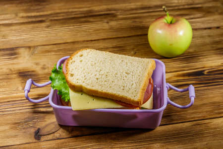 Lunch box with sandwiches and apple on a wooden table 免版税图像