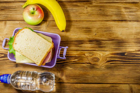 Lunch box with sandwiches, bottle of water, banana and apple on a wooden table. Top view, copy space