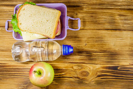 Lunch box with sandwiches, bottle of water and apple on a wooden table. Top view, copy space