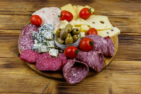 Antipasti platter with olives, cherry tomatoes, assortment of italian salami and cheese on a wooden table