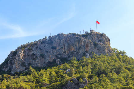 View of Chalysh mountain with Turkish flag in Kemer, Turkey