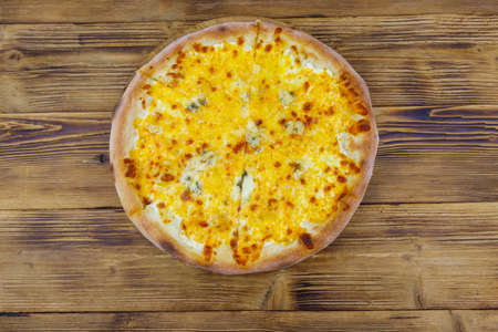 Pizza Four cheese on a wooden background. Top view Banco de Imagens