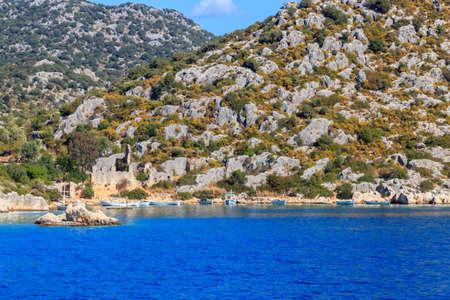 Boats moored at rocky shore of the Mediterranean Sea near Simena in Antalya province, Turkey