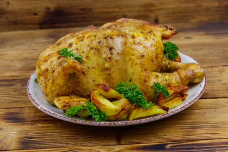 Baked whole chicken with potato on a wooden table Banco de Imagens