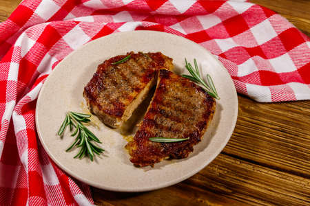 Grilled pork steaks with rosemary on wooden table