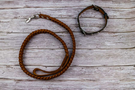 Brown leather leash and spiked collar for dog on wooden background. Top view 免版税图像