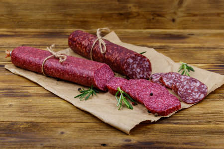 Salami sausages on craft paper on a wooden table