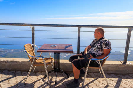 Man relax in cafe on a top of Tahtali mountain near Kemer, Antalya Province in Turkey