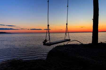 Rope swing on a shore of the Dnieper river in Ukraine at sunset