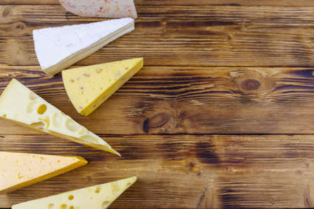 Set of various types of cheese on wooden table. Top view, copy space