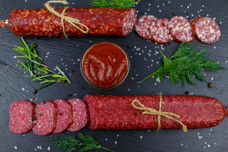 Salami sausages with ketchup and spices on black slate board. Top view
