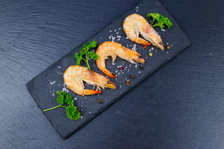 Big raw red prawns with parsley, salt and pepper on a slate board on black background. Top view