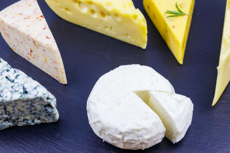 Set of various types of cheese on black slate background 免版税图像