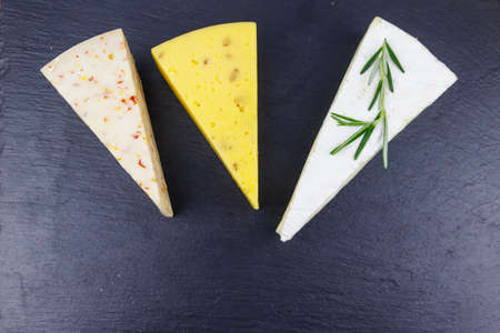 Set of various types of cheese on black slate background. Top view