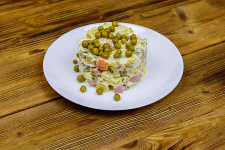 Traditional Russian festive salad Olivier on wooden table 免版税图像