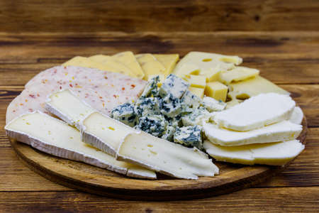 Cheese platter with different kinds of cheese on wooden table