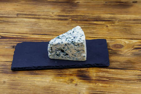 Blue cheese with mold on serving black slate board on wooden table