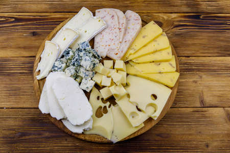 Cheese platter with different kinds of cheese on wooden table. Top view