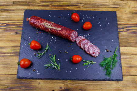 Salami sausage with cherry tomatoes and spices on black slate board on a wooden table