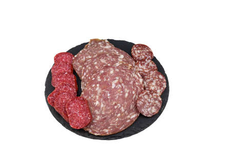 Different tasty sliced salami sausage on a black slate serving board isolated on white background