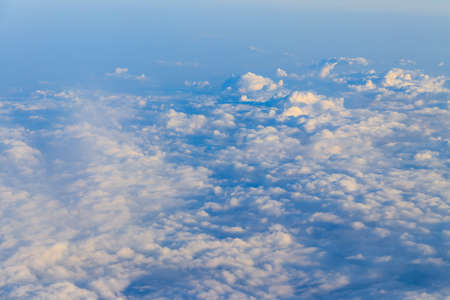 Beautiful white clouds in blue sky. View from airplane