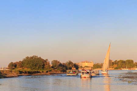 Luxor, Egypt - December 11, 2018: Tourist boats sailing on the Nile river in Luxor, Egypt Редакционное