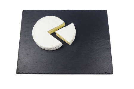 Piece of brie cheese on black slate board isolated on white background Фото со стока