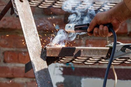 Worker welding the steel part by manual Фото со стока