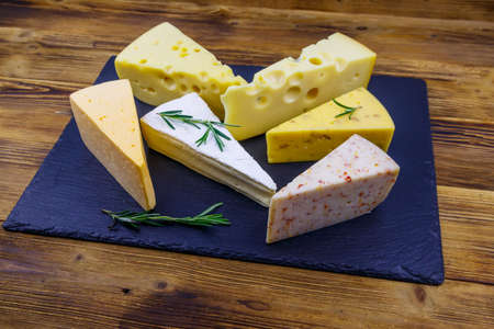 Set of various types of cheese on black slate board on a wooden table Фото со стока