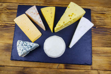 Set of various types of cheese on black slate board on a wooden table. Top view Фото со стока