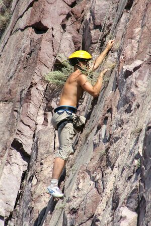 clinging: climber climbing on a rock