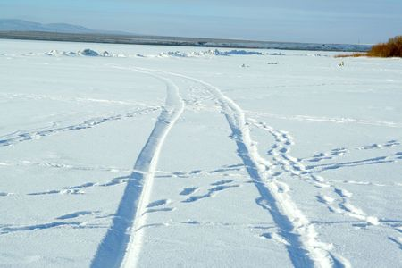 sidelit: Abstract design - tire tracks in snow Stock Photo
