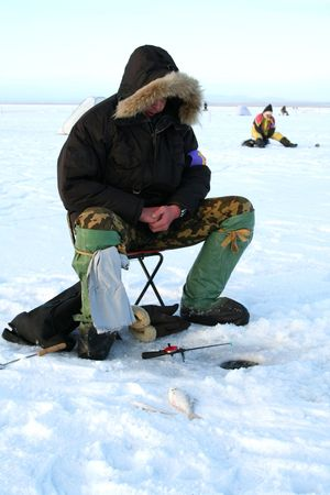 Fishing on an ice of the frozen lake photo